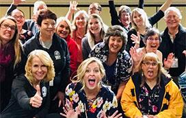 Megan Bryant and group participants of a improv business workshop smiling together
